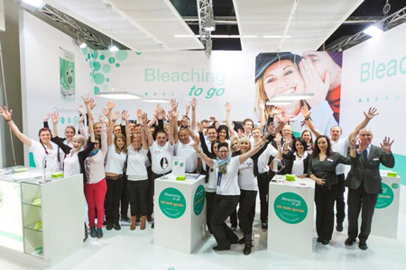 Heinz Seidl's team gets hyped at the Ultradent booth at a trade show.